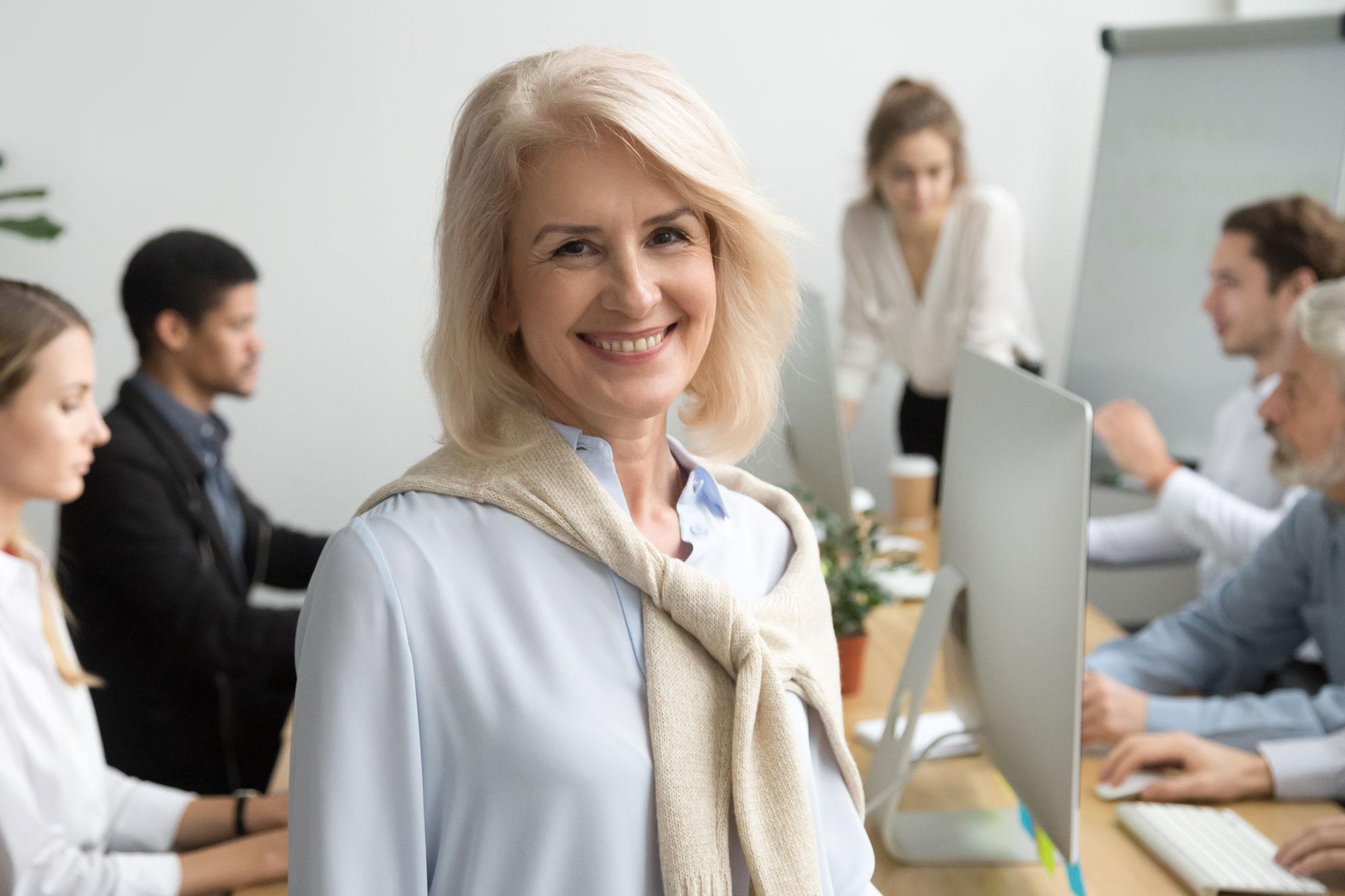 Lächelnde Unternehmerin vor ihrem Team